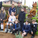 St. Helen's School children visit the cemetery and join local residents in the fox sculpture corner - just one of several improved areas in the cemetery.
