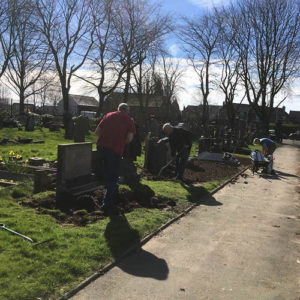 Following memorial improvements volunteers weed and prepare the ground for grass seeding.