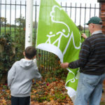 The Friends youngest and oldest volunteers raise the Green Flag.