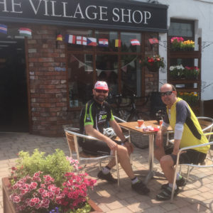 Cyclists enjoy the sun and refreshments in the shops's outdoor cafe area.