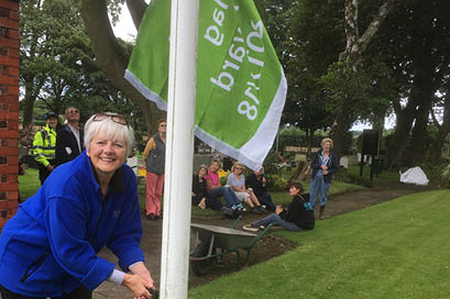 Chair Mandy Eccles proudly raises the 2017-2018 Green Flag - July 2017.