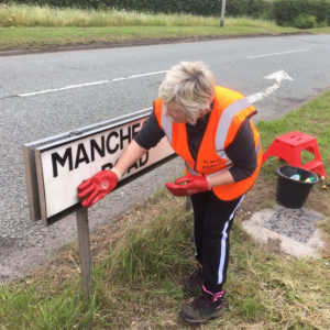 Community Plan volunteer helps at the sign cleaning action day Hollins Green - 1st June 2019.